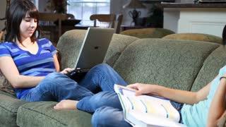 young girls studying on sofa pan