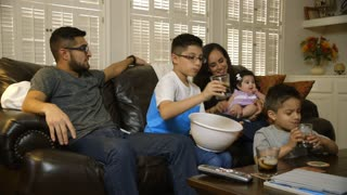 young hispanic family eating popcorn and watching tv