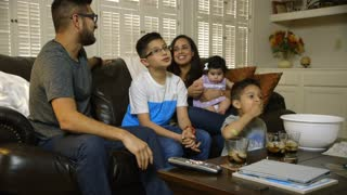 young hispanic family watching tv