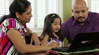 Young Indian family using a laptop