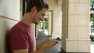 young man outdoor texting on his smart phone.