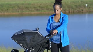 young mother at the park with her baby in the stroller