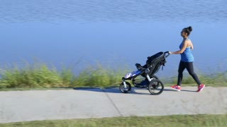 young mother exercising with her baby in the stroller