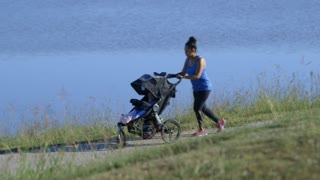 Young mother jogging next to a lake with her baby