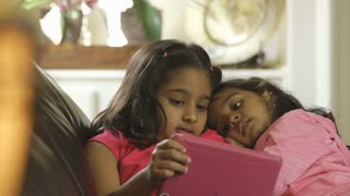 Young sisters watching something on a tablet pc in their house