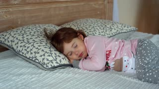 A happy little girl in pajamas lying on bed