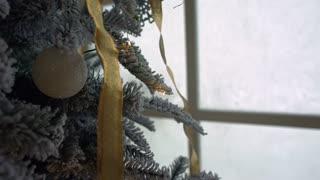 Christmas ornament on tree with bokeh lights.