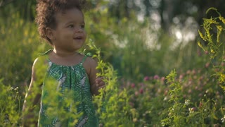 Handsome African-American child in the green grass on the nature