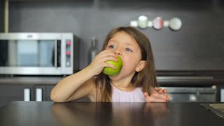 Little girl eating a green apple and smiling