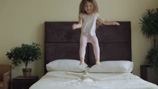 Little girl jumping on the bed at home