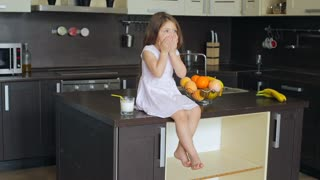 Little girl sitting on the kitchen table