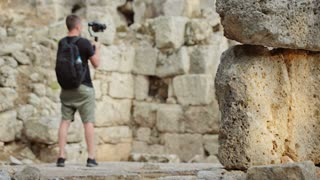 A traveler shoots video footage in the Ruins of the Antique City