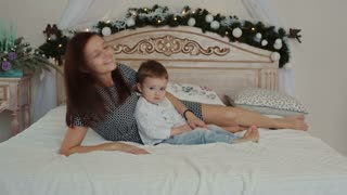 A young mother and her son lying on the bed