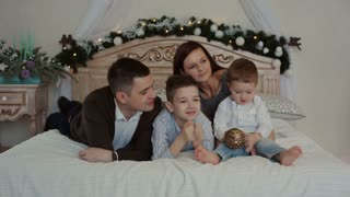 Happy young family lying on the bed.