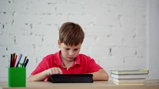 The schoolboy looks at the tablet