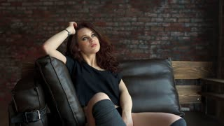 Young sexy girl on leather couch