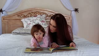 Young beautiful mother reads a book with her little daughter