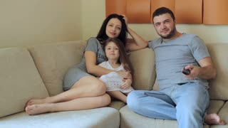 Young family watching television sitting on sofa