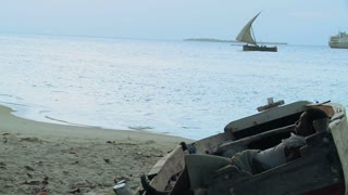 A boy sleeps in a hammock while a dhow sailboat sails by in the distance, Zanzibar.