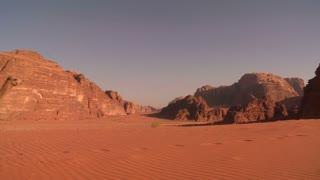 A camel train passes directly over the camera in the Saudi desert of Wadi Rum, Jordan.