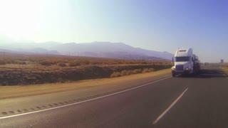 A car carrier truck moves across the desert in this POV shot.