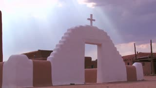A Christian cross glows against a heavenly sky at the Taos pueblo.