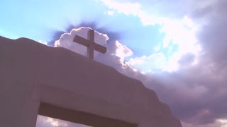A Christian cross glows against a heavenly sky.