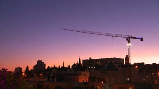 A construction crane towers in front of the old city walls of Jerusalem, Israel by night.