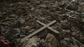 A cross sits amongst the scattered clothing of victims following a genocide in a church in Rwanda.