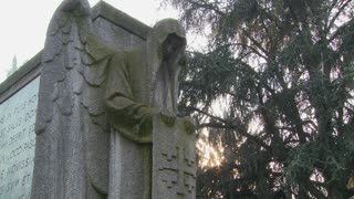 A ghostly angel looks down on a grave from above.