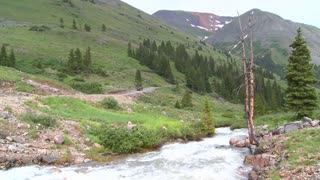 A jeep drives through wilderness in the Colorado Rockies.