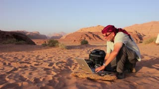 A man works on a laptop computer in the middle of the desert.