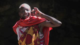 A Masai man in tribal costume talks on a cell phone.