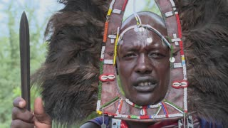 A Masai warrior in full headdress and spear.