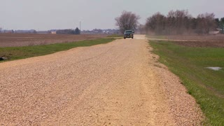 A pickup truck drives on a dirt road through Midwest farmland.