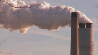 A power plant with smokestacks belches smoke into the air.