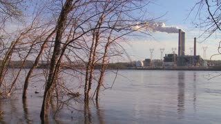 A power plant with smokestacks near a river.