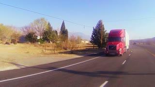 A red 18 wheeler truck moves across the desert in this POV shot.