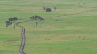 A safari jeep travels on a distant road in Africa.