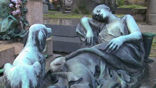 A sculpture in a cemetery depicts a loyal dog waiting for its owner to wake up.