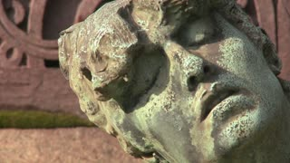A sculpture in a cemetery seems to be suffering.
