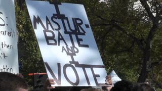 A sign at a rally says I Masturbate and I Vote.