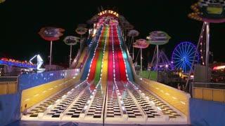A slide at a carnival at night.