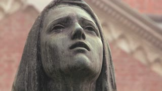 A statue of a woman weeping in a cemetery or church.