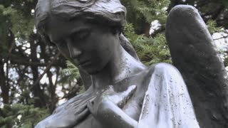 A statue of an angel stands over a grave in a cemetery.