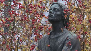 A statue of an artist appears to be thinking or contemplating.