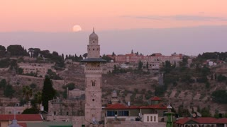 A time lapse view over the city skyline of the old city of Jerusalem with the moon rising.