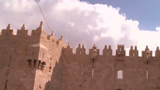 A timelapse shot of clouds moving over the gates and walls of the Old City of Jerusalem.