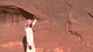A traditional Bedouin points out ancient and mysterious petroglyphs depict humans and camels in the Saudi desert near Wadi Rum, Jordan.