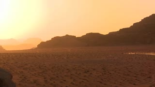 A trail of dust follows a vehicle into the sunset across the desert in Wadi Rum, Jordan.